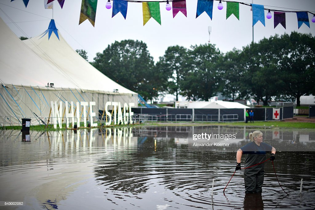 A member of the German Technical Emergency Service (THW) stands in a puddle in front of the White Stage at the Hurricane Festival compound on June 25, 2016 in Scheessel, Germany. The Hurricane Festival was evacuated yesterday and was delayed today for the late evening, following heavy rain and thunderstorm alerts. The rain and thunderstorm have hit the festival during the night and day, causing damage to tents and flooded the festival site, only 7 concerts can be played on two stages today. The Hurricane Festival celebrates this year its 25th anniversary. 75.000 music fans have visited the Festival, but some thousands have already left the compound due to the current situation.