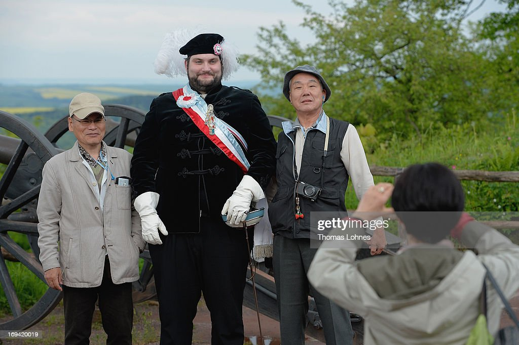 A member of the German traditional university fraternities, in German called Burschenschaften, pose with japanese tourists before the ceremony at the Wartburg castle on May 24, 2013 in Eisenach, Germany. The Burschenschaftenm, who are holding thier annual meeting in Eisenach, originated in 1815 among university students who volunteered to fight Napoleon.
