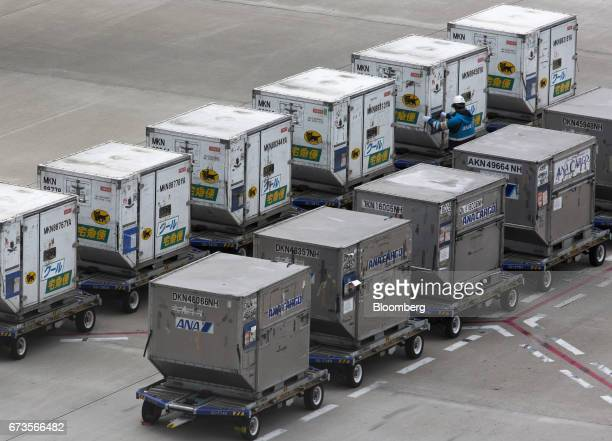 A member of the ground crew for All Nippon Airways Co checks a Yamato Holdings Co cargo container at Haneda Airport in Tokyo Japan on Wednesday April...