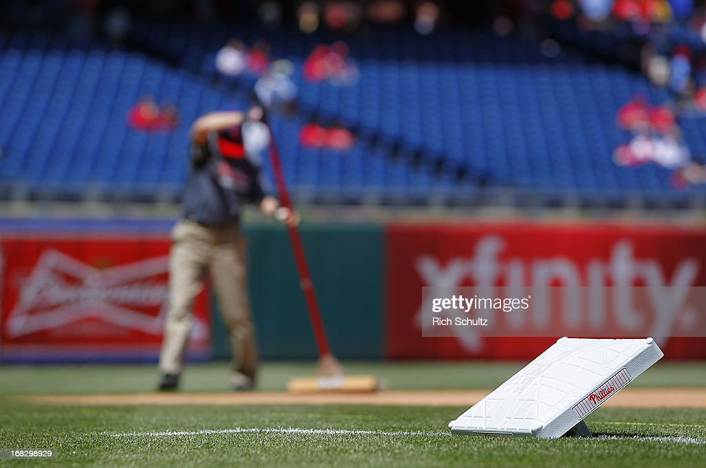 A member of the ground crew sweeps the infield as third base waits to be installed before the start of a game between the Miami Marlins and Philadelphia Phillies on May 5, 2013 at Citizens Bank Park in Philadelphia, Pennsylvania.