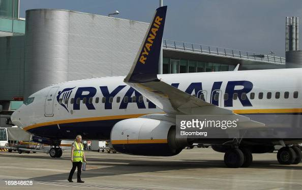 A member of the ground crew walks near a passenger aircraft operated by Ryanair on the tarmac at Manchester Airport in Manchester UK on Friday May 31...