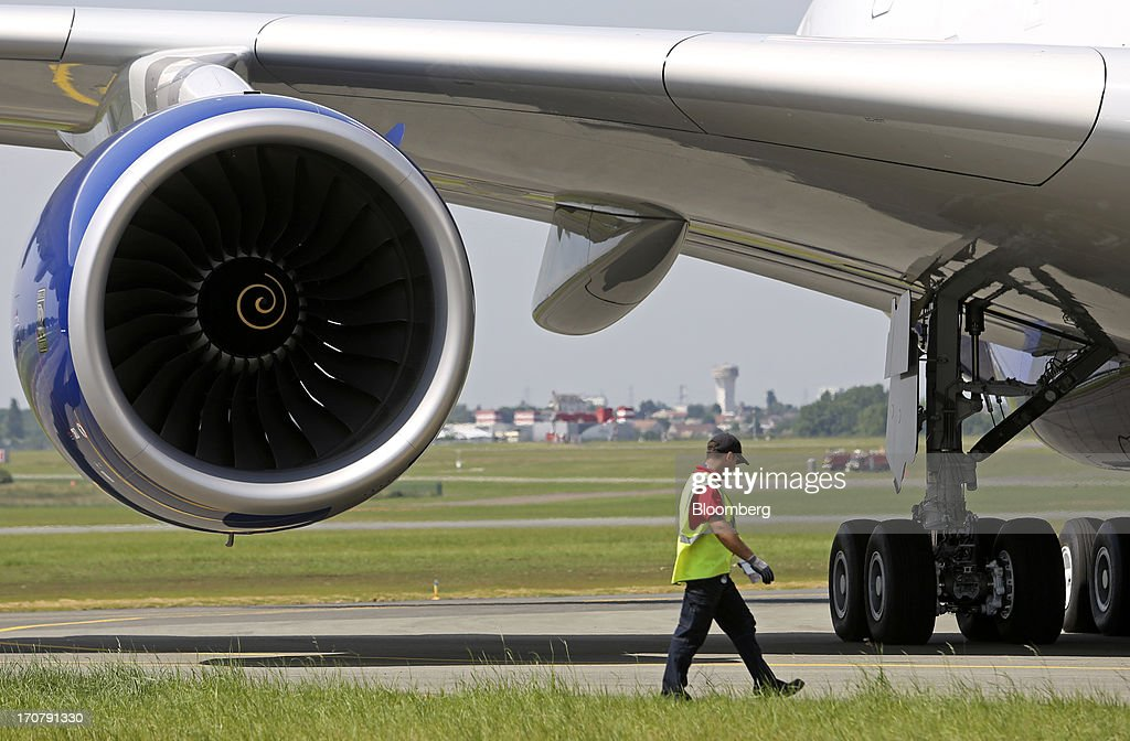A member of the ground crew walks near the Rolls-Royce Holdings Plc Trent 900 engine of an Airbus SAS A380 aircraft, operated by British Airways, on the first day of the Paris Air Show in Paris, France, on Monday, June 17, 2013. The 50th International Paris Air Show is the world's largest aviation and space industry show, and takes place at Le Bourget airport June 17-23. Photographer: Chris Ratcliffe/Bloomberg via Getty Images