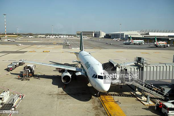 A member of the ground crew works beneath an Alitalia SpA aircraft as it stands at a departure gate at Fiumicino airport in Rome Italy on Friday...