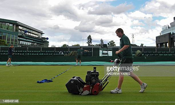A member of the ground staff mows the grass on a court on the eve of the start of the 2012 Wimbledon Championships tennis tournament at the All...