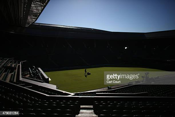 A member of the ground staff mows the grass on centre court on day two of Wimbledon tennis tournament on June 30 2015 in London England The 129th...