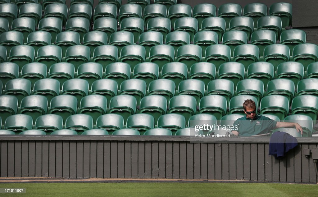 A member of the ground staff sits in Centre Court ahead of play on day four of the Wimbledon Lawn Tennis Championships at the All England Lawn Tennis and Croquet Club on June 27, 2013 in London, England.