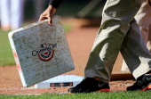 A member of the grounds crew changes the bases during the seventh inning of the Opening Day game between the Baltimore Orioles and the Boston Red Sox...
