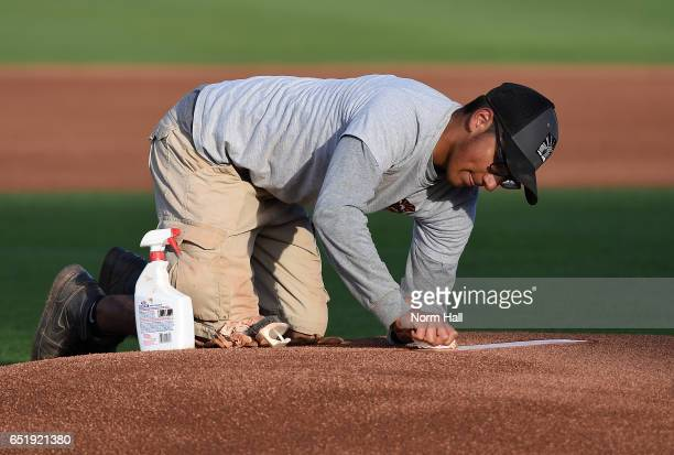A member of the grounds crew cleans the pitching rubber on the mound prior to a game between the Colorado Rockies and the Cincinnati Reds at Goodyear...