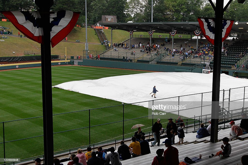A member of the grounds crew inspects the tarp during a rain delay before the start of the Little League World Series championship game between the Japan team from Hamamatsu City, Japan and the West team from Huntington Beach, California on August 28, 2011 in South Willamsport, Pennsylvania.