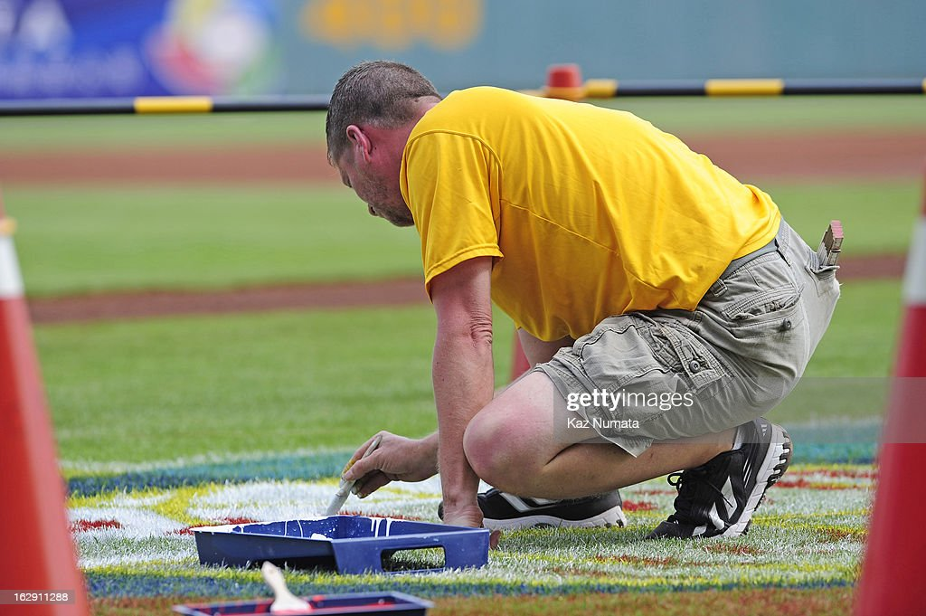 A member of the grounds crew paints the World Baseball Classic logo on the field during the World Baseball Classic workout day at Taichung Intercontinental Baseball Stadium on March 1, 2013 in Taichung, Taiwan.
