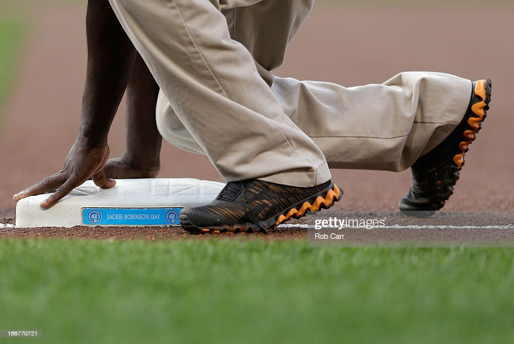 A member of the grounds crew puts down the first base bag honoring Jackie Robinson Day before the start of the Baltimore Orioles and Tampa Bay Rays game Oriole Park at Camden Yards on April 16, 2013 in Baltimore, Maryland.