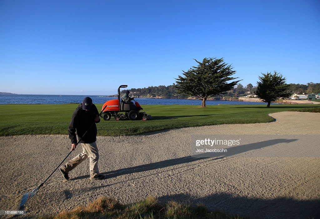 A member of the grounds crew rakes a bunker on the 18th hole during the third round of the AT&T Pebble Beach National Pro-Am at Pebble Beach Golf Links on February 9, 2013 in Pebble Beach, California.