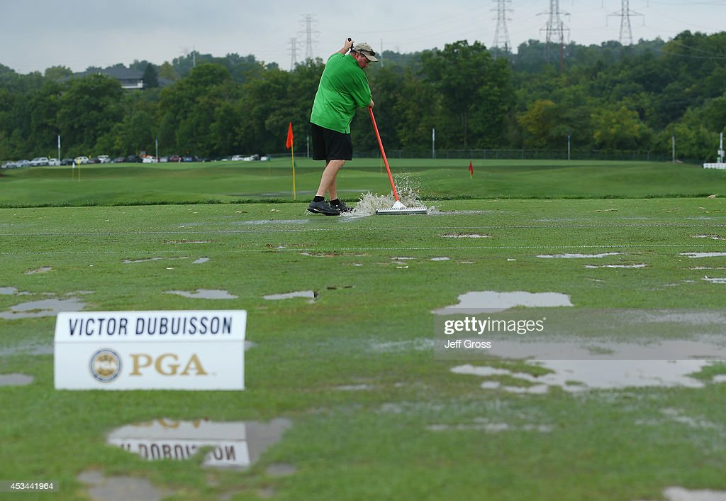 A member of the grounds crew squeegees the practice ground during a weatherdelayed final round of the 96th PGA Championship at Valhalla Golf Club on...