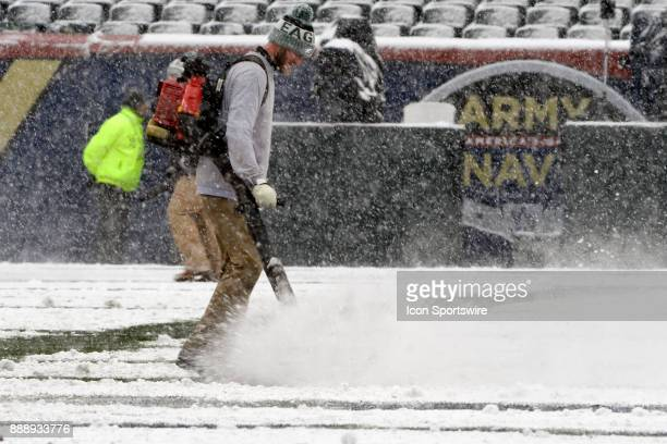 A member of the grounds crew uses a blower to blow snow off the field on December 9 2017 at Lincoln Financial Field in Philadelphia Pa in the 118th...