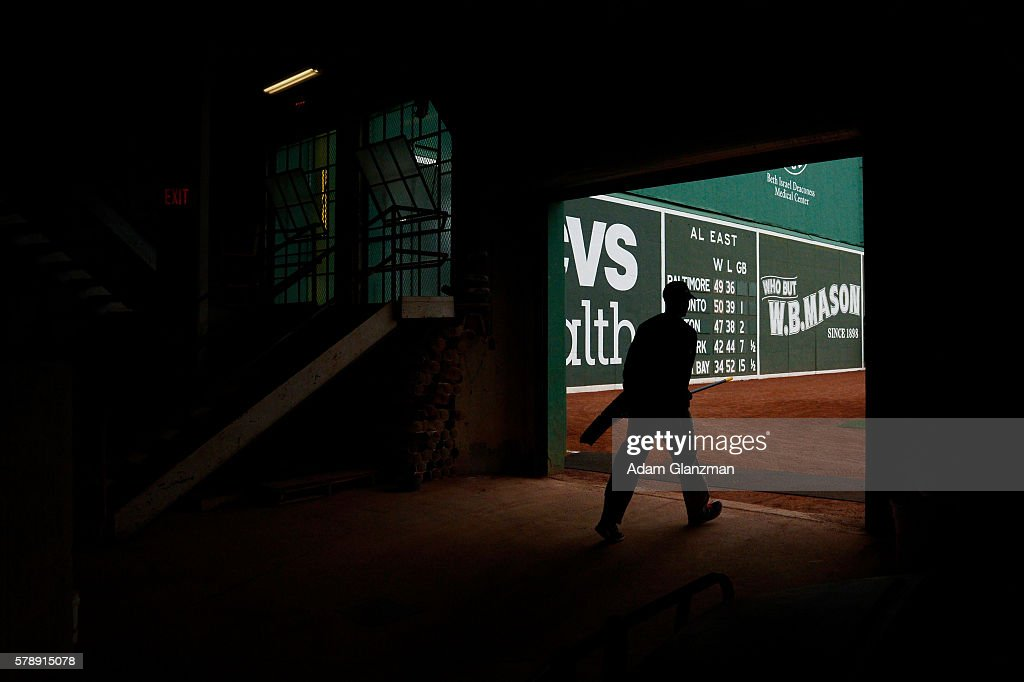 A member of the grounds crew walks along the green Monster prior to the Boston Red Sox vs Tampa Bay Rays game at Fenway Park on July 9 2016 in Boston...