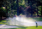 A member of the grounds crew waters the course during the second round of the 2014 Masters Tournament at Augusta National Golf Club on April 11 2014...