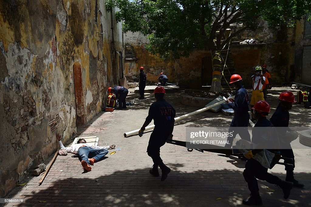 A member of the Haitian Civil Protection rescues a victim during an Earthquake and Tsunami Emergency drill in the city of Cap-Haitien, on May 6, 2016. The simulation exercise was organised by the Civil Protection Directorate, with the support of the UN Development Programme (UNDP). An estimated 4,500 people participated in the activities during the simulacre. / AFP / HECTOR