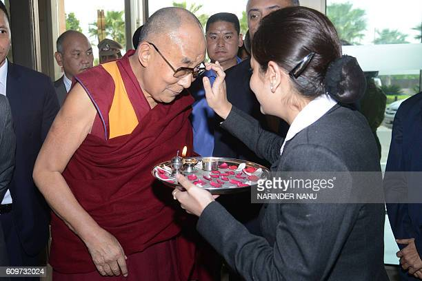 TOPSHOT A member of the hotel staff places a tilak on the forehead of Tibetan spiritual leader the Dalai Lama on his arrival at a hotel in Amritsar...
