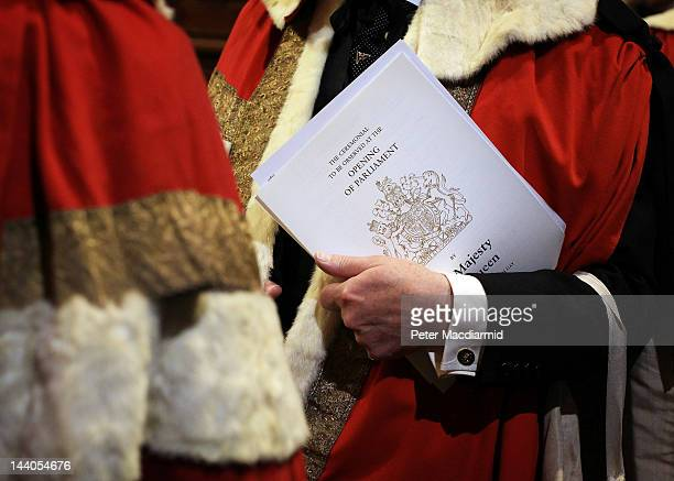 A member of The House of Lords carries a programme of events as he stands in the Prince's Chamber before the State Opening of Parliament on May 9...