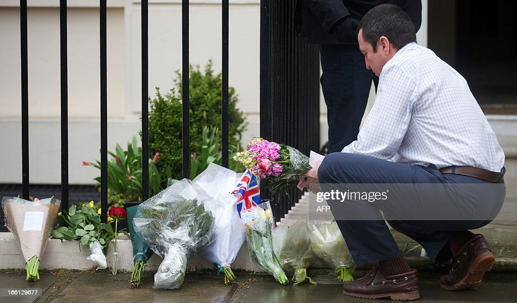 A member of the household of former British Prime Minister Margaret Thatcher gathers flowers and tributes left by members of the public outside Thatcher's London home on April 9, 2013. Mikhail Gorbachev, Helmut Kohl and Bill Clinton were among the former friends and foes who joined in tributes to Margaret Thatcher, praising the fearlessness and fierce determination of an 'iconic' leader.