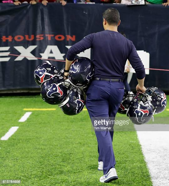 A member of the Houston Texans carries helmets to the locker room after the NFL game between the Indianapolis Colts and the Houston Texans at NRG...