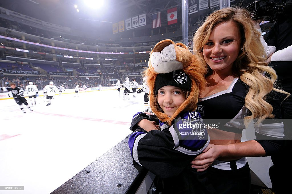 A member of the Ice Crew and a young fan stand on the bench prior to the game between the Los Angeles Kings and the Dallas Stars at Staples Center on March 7, 2013 in Los Angeles, California.