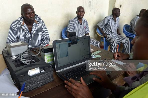 A member of the Independent Electoral and Boundaries Commission registers a Kenyan prisoner to vote for this year Kenyan general election at the...