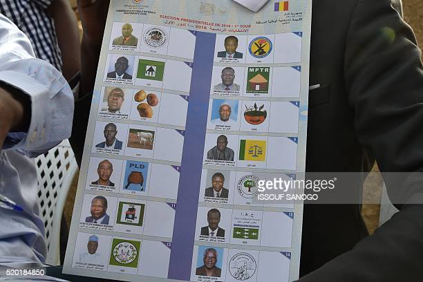 A member of the Independent National Electoral Commission holds a poster bearing the portraits of all the presidential election candidates at a...