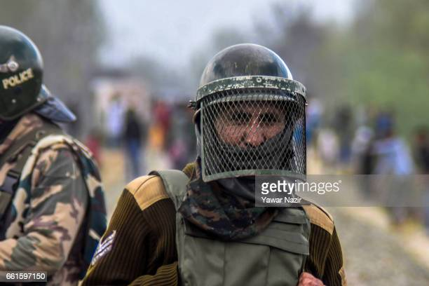 A member of the Indian government forces looks on as Kashmiri Muslim protesters throw stones during an anti India protest against the recent civilian...