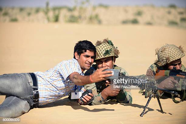 A member of the Indian media takes a selfie photograph with a soldier during army exercises in the Thar Desert in the western state of Rajasthan on...
