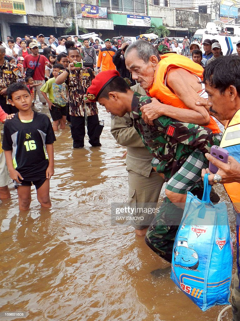 A member of the Indonesian military (C) carries an elderly man as the army helps evacuate people after their homes were flooded by season rains in Jakarta on January 18, 2013. Floods in Indonesia's capital Jakarta have left at least 11 people dead, authorities said on January 18 as murky brown waters submerged parts of the city's business district, causing chaos for a second day. AFP PHOTO / Bay ISMOYO