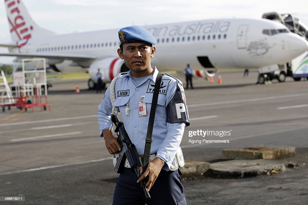 A member of the Indonesian military stands guard near a Virgin Australia airplane, which was forced to land at International Ngurah Rai Airport after the pilot sent a distress signal on April 25, 2014 near Denpasar, Bali, Indonesia. Early reports suggested an attempt to hijack a Virgin Australia had occured mid-flight, although Virgin has since clarified that the disturbance was caused by a drunk passenger acting aggressively and attempting to enter the cockpit.