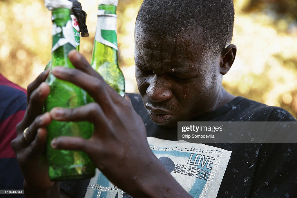 A Member of the Indumiso Yamakholwa In Zion church prays while holding used bottles containing blessed water and a written prayer during a ceremony in the Yeoville neighborhood June 21, 2013 in Johannesburg, South Africa. After being prayed over and blessed, worshipers will smash the bottles to release the prayers to God. The worn, arid space on top of the Yeoville hill offers worshipers of various Christian denominations from South African, Botswana, Zimbabwe, the Democratic Republic of Congo and other African nations an open-air space where they can publicly practice their faith with a scenic view of downtown Johannesburg.