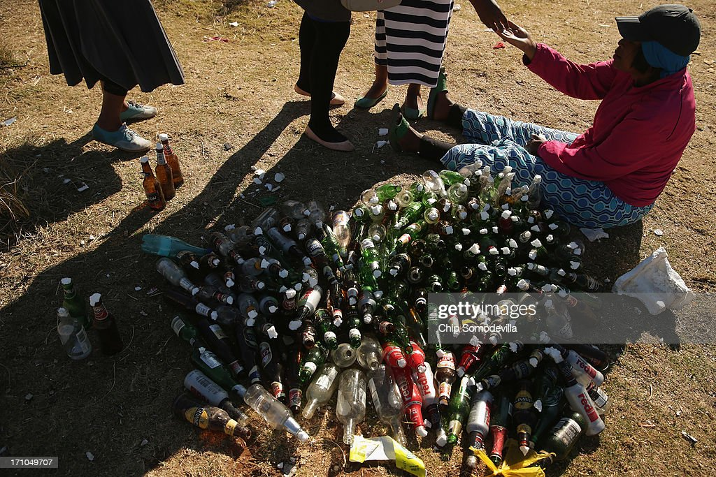 A member of the Indumiso Yamakholwa In Zion church sells used bottles which will be filled with written prayers and water before a prayer service in the Yeoville neighborhood June 21, 2013 in Johannesburg, South Africa. After being prayed over and blessed, worshipers will smash the bottles to release the prayers to God. The worn, arid space on top of the Yeoville hill offers worshipers of various Christian denominations from South African, Botswana, Zimbabwe, the Democratic Republic of Congo and other African nations an open-air space where they can publicly practice their faith with a scenic view of downtown Johannesburg.