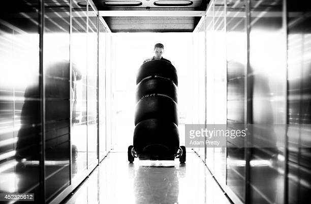 A member of the Infiniti Red Bull Racing team pushes tyres into the garage during previews ahead of the German Grand Prix at Hockenheimring on July...
