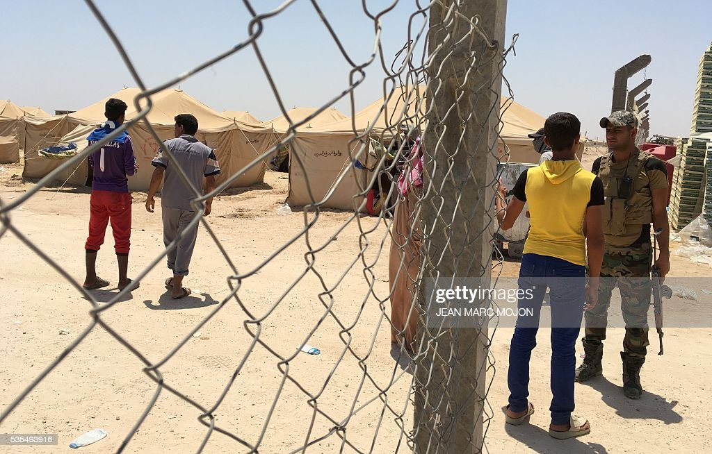 A member of the Iraqi armed forces stands guard at the entrance of a newly-opened camp in the government-held town of Amriyat al-Fallujah 50 kilometres (30 miles) southwest of Baghdad, on May 29, 2016, which was set up to shelter people fleeing violence around the city of Fallujah. The Norwegian Refugee Council, which runs the camp in Amriyat al-Fallujah, says around 3,000 people have managed to flee the area and reach displacement camps since Iraqi forces launched an operation against the Islamic State a week ago. The biggest wave of arrivals so far was Saturday night and included mostly exhausted and hungry women and children. / AFP / Jean Marc MOJON