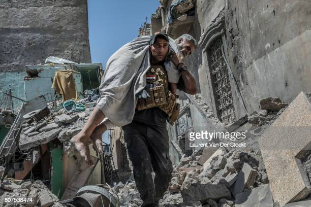 A member of the Iraqi armed services carries an elderly man from the rubble of alNuri mosque complex in Mosul Iraq on June 29 2017 The Iraqi Army...