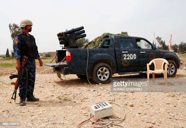 A member of the Iraqi army's 9th Division prepares to fire a multiple rocket launcher at a position in western Mosul on April 8 during a military...