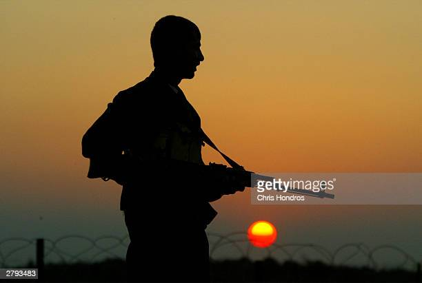 A member of the Iraqi Civil Defense Corps halts a car at a checkpoint December 8 2003 in near Samarra Iraq US forces want the nascent Iraqi Civil...
