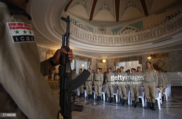 STORY 'IRAQUSDEFENSE' A member of the Iraqi Civil Defense Corps holds his weapon in front of new ICDC graduates at a former palace of ousted leader...