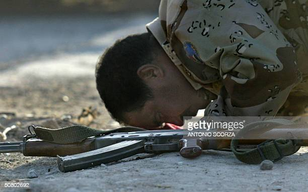 A member of the Iraqi Civil defense Corps prays at a joint checkpoint with US soldiers at the entrance of the restive city of Fallujah 05 May 2004...