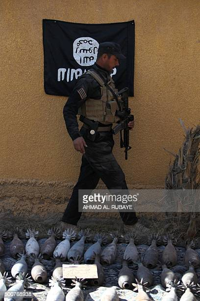 A member of the Iraqi counterterrorism forces walks near mortar shells and a flag of the Islamic State jihadist group found in an arms depot that...