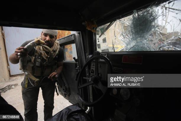 TOPSHOT A member of the Iraqi counterterrorism service forces displays an explosive belt taken off the dead body of a reported Islamic State group...