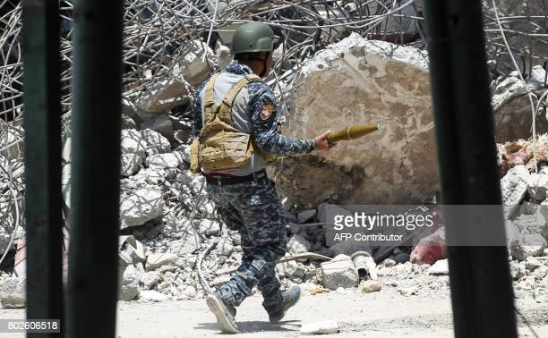 A member of the Iraqi federal police carries a rocketpropelled grenade launcher while advancing past the rubble through the Old City of Mosul on June...
