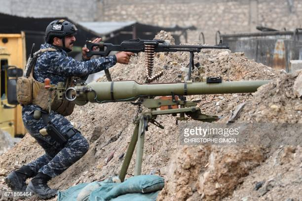 A member of the Iraqi Federal Police fires towards positions held by the Islamic State group on the front line of the attack on West Mosul on April...