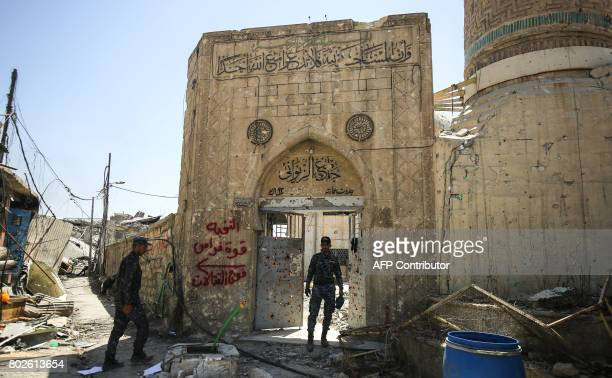 TOPSHOT A member of the Iraqi federal police stands through the doorway leading into the damaged historic 19th cenury Ziwani mosque in the Old City...