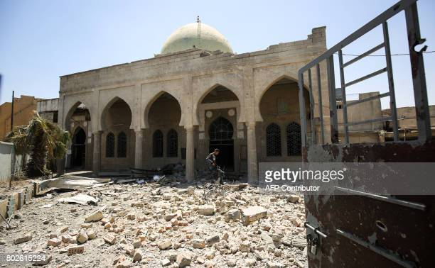 A member of the Iraqi federal police walks through the rubble in the grounds outside the damaged historic 19th century Ziwani mosque in the Old City...