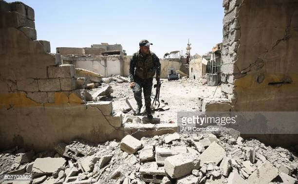 TOPSHOT A member of the Iraqi federal police walks through the rubble of a destroyed building during the advance through the Old City of Mosul on...