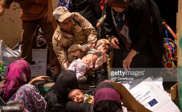 A member of the Iraqi forces carries a child as women who fled the fighting with Islamic State group jihadists in the Old City of Mosul move their...
