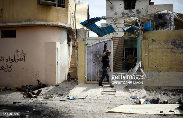 A member of the Iraqi forces carries a rocket launcher as he walks down a street near the frontline in west Mosul on 21 April during the Iraqi...